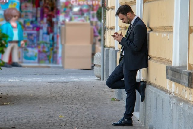 A businessman staring at his phone while leaning on a wall